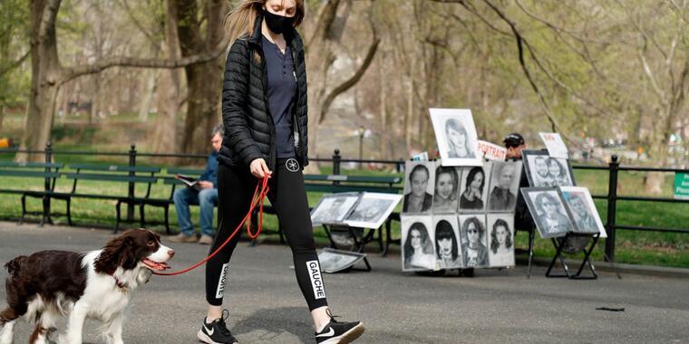 Una mujer con mascarilla pasea a su perro en Central Park
