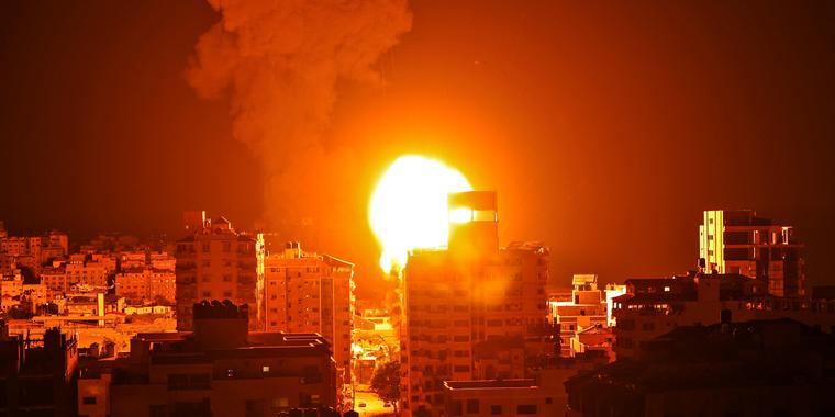 Una bola de fuego y una columna de humo se elevan sobre los edificios de la ciudad de Gaza.