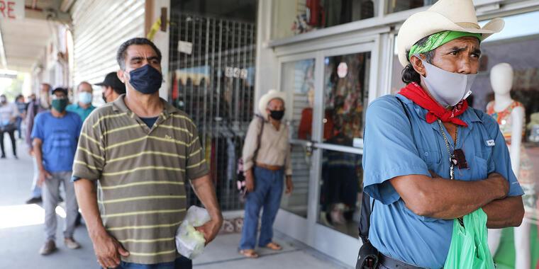 Faustino (R), quien actualmente está desempleado, espera en una fila socialmente distanciada para ingresar a una tienda de libros cerca de la frontera entre Estados Unidos y México en el condado de Imperial, que ha sido severamente afectado por la pandemi
