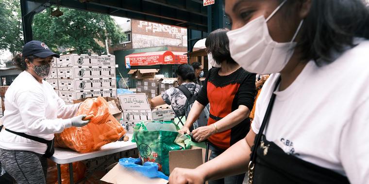 Las personas reciben alimentos de una organización benéfica local en el distrito de Queens el 4 de junio de 2021 en la ciudad de Nueva York.