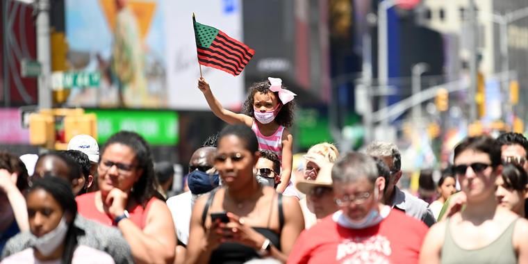 Una niña ondea una bandera afroamericana durante el Broadway Celebrates Juneteenth en Times Square el 19 de junio de 2021 en la ciudad de Nueva York.