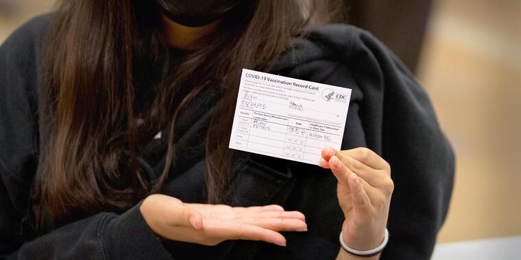 Una chica muestra su tarjeta de prueba de vacunación contra el COVID-19.