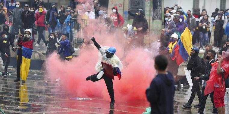 Un manifestante devuelve una lata de gas lacrimógeno a la policía durante los enfrentamientos en Bogotá, Colombia, el miércoles 5 de mayo de 2021.