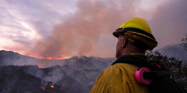 Un bombero observa la columna de humo del incendio en Pacific Palisades, una zona de Los Ángeles, el 15 de mayo de 2021.