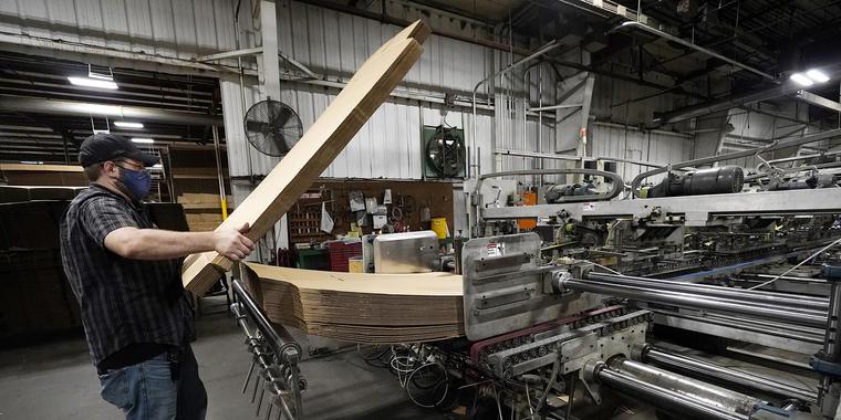 Rob Bondurant, supervisor de Great Southern Industries, una empresa de embalaje, carga una máquina de acabados de madera en las instalaciones de Jackson, Mississippi, viernes 28 de mayo de 2021.