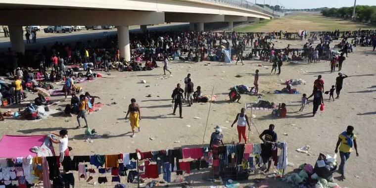Migrantes esperan bajo el Puente Internacional Del Río a ser procesados por las autoridades fronterizas