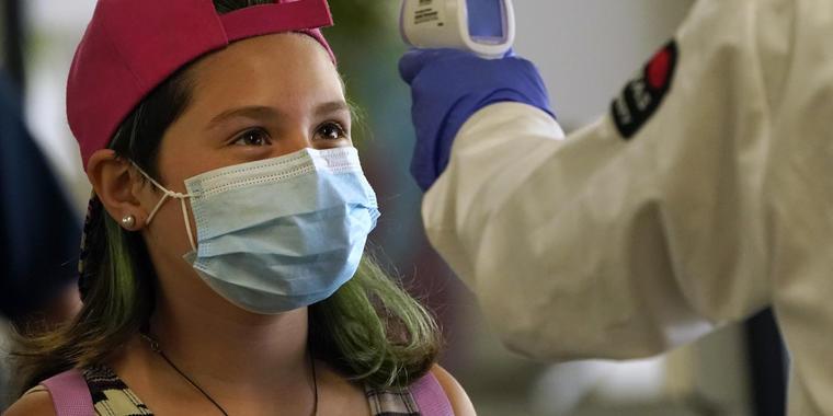 Control de temperatura a una joven con mascarilla en California.