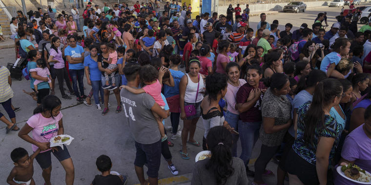 Solicitantes de asilo enviados de regreso a México bajo el programa MPP esperan en fila para obtener comida el viernes 30 de agosto de 2019, en un campamento cercano el Puente Internacional Gateway en Matamoros, México.