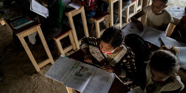 Niños estudiantes en aula improvisada instalada en un sitio de construcción en 2019