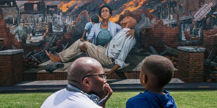 Un hombre le enseña a un niño sobre la masacre de Tulsa, en el distrito de Greenwood, el 28 de mayo de 2021 en Tulsa, Oklahoma. Este año, el 31 de mayo, se cumple el centenario desde que una turba blanca atacó ese vecindario, matando a cientos de personas