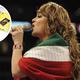 Jenni Rivera cantando con reboso con colores mexicanos.