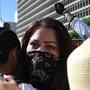 Unos manifestantes se abrazan mientras negros, latinos e indígenas se reúnen frente al Ayuntamiento después de marchar durante la Marcha de la Unidad de Comunidades de Color el 12 de julio de 2020 en Los Ángeles, California. La marcha busca unir a las com