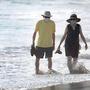 Una pareja con tapabocas camina por la playa durante una ola de calor mientras continúa el brote del coronavirus, en Pacific Palisades, California, 19 de agosto de 2020.