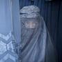 Una mujer afgana mira por la rendija de su burqa mientras espera para probarse una nueva burqa en una tienda en Kabul, Afganistán, el 11 de abril de 2013.