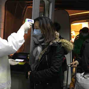 Oficiales de salud revisan a los pasajeros en el aeropuerto de Beijing, China.