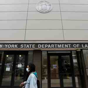 A person walks by the entrance of the New York State Department of Labor offices, which closed to the public due to the coronavirus disease (COVID-19) outbreak in the Brooklyn borough of New York City