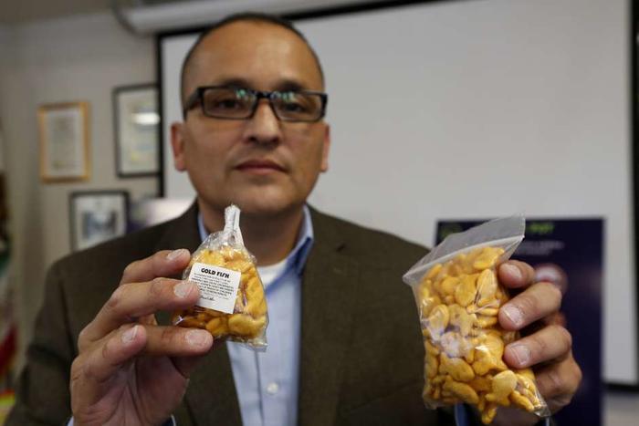 Albert Melena muestra paquetes de golosinas a base de marihuana y regulares, que son muy similares, incluso en los nombres.