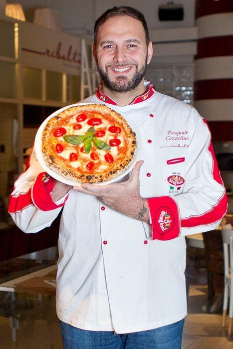 Chef presentando una pizza margarita