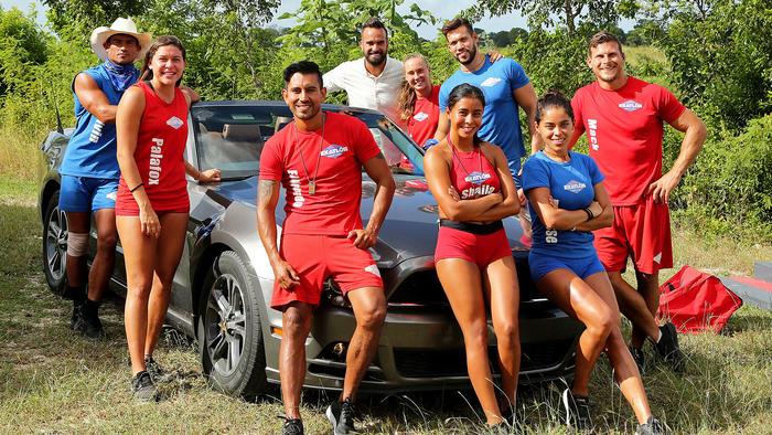 Los ocho finalistas y Erasmo posan con el auto deportivo