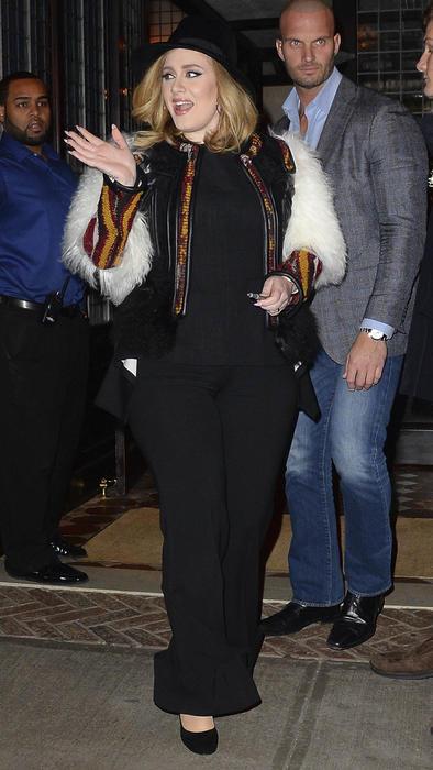Adele saludando con sombrero negro y chal peludo blanco