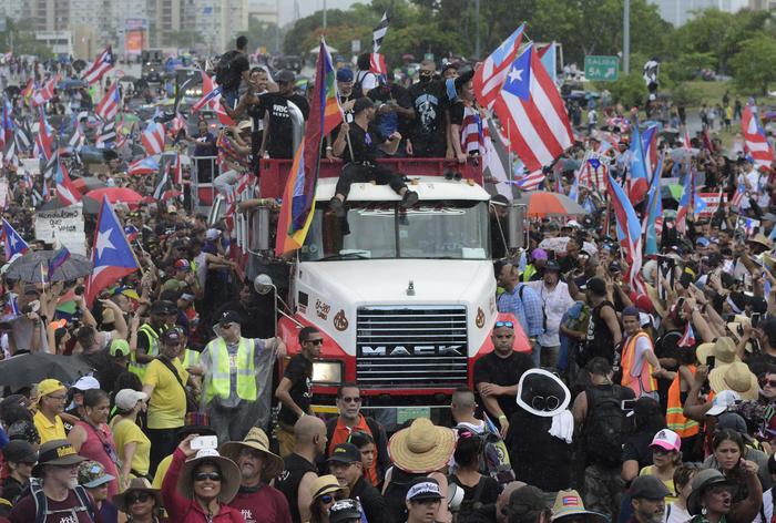 El cantante puertorriqueño Ricky Martin, al frente en el techo del camión, participa con otras celebridades locales en una protesta para exigir la renuncia del gobernador Ricardo Rosselló, en San Juan, Puerto Rico, el lunes 22 de julio de 2019.