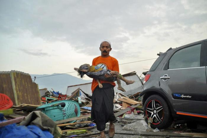 Un hombre lleva el cuerpo de un niño que murió en el tsunami en Palu, Sulawesi Central, Indonesia. (Foto AP / Rifki, archivo)