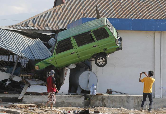 Un auto queda alojado en una casa tras ser arrojado por las enormes olas que provocó el tsunami en Indonesia.