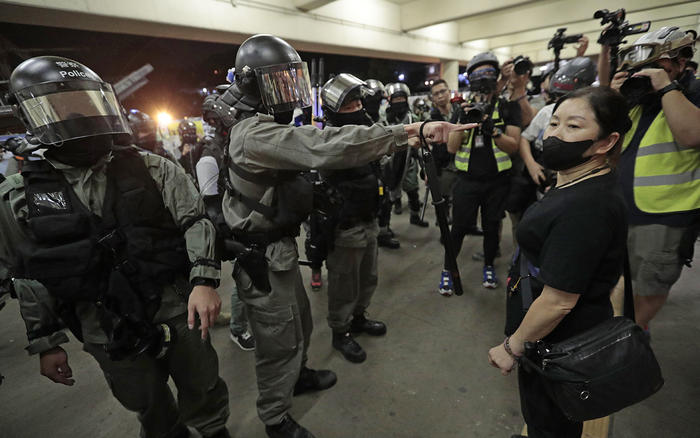 La policía antidisturbios le pide a una mujer que se quite la máscara frente a una estación de tren en Hong Kong, el 3 de noviembre de 2019. La policía irrumpió en varios centros comerciales en un intento por frustrar más protestas en favor de la democrac