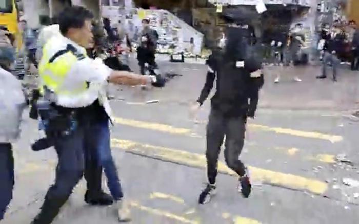 En esta imagen tomada de un video, un oficial de policía, a la izquierda, se prepara para disparar contra un manifestante, en Hong Kong el 11 de noviembre. El policía disparó contra el manifestante cuando los manifestantes bloquearon las líneas y líneas d