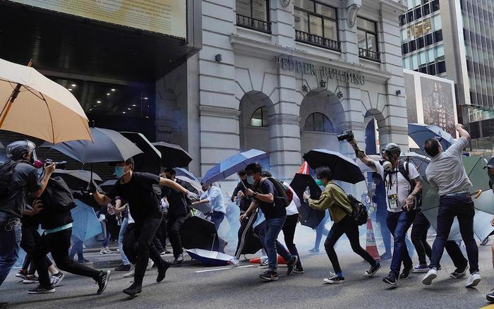 Manifestantes con paraguas corren después de que les lancen gases lacrimógenos, Hong Kong, el 11 de noviembre.