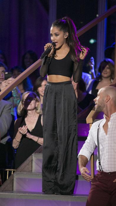 Ariana Grande con crop top negro y pantalón de tiro alto