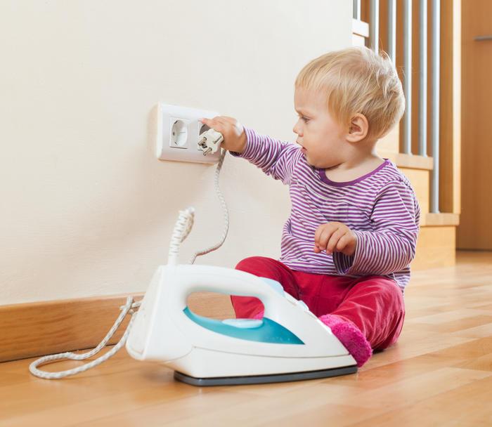 Bebé jugando con un enchufe
