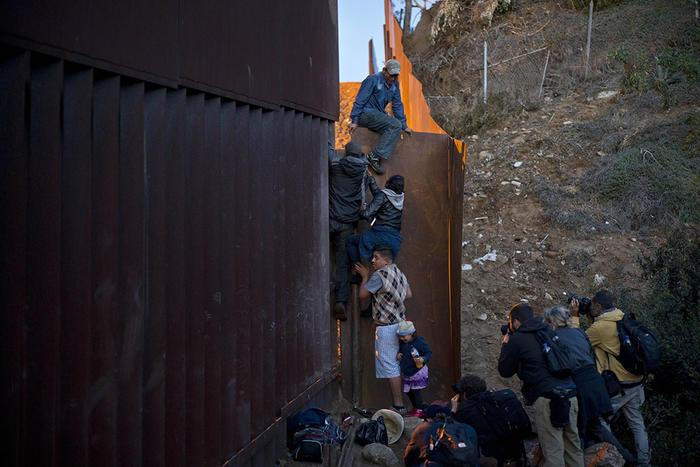 un migrante hondureño ayuda a otros a cruzar el muro entre méxico y estdos unidos.