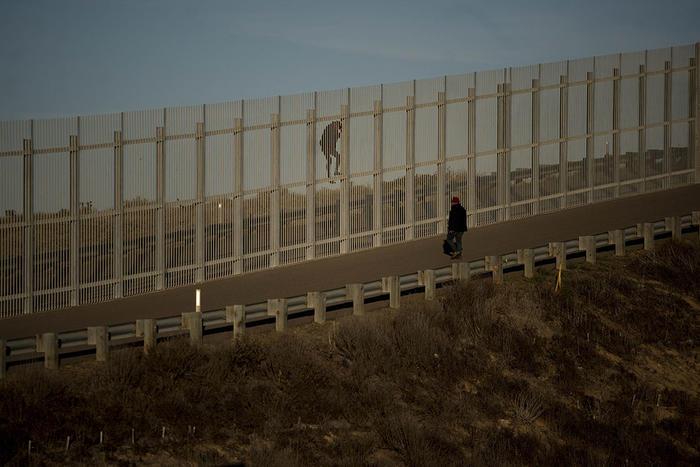 dos migrantes intentan cruzar la cerca que separa a méxico y estados unidos.