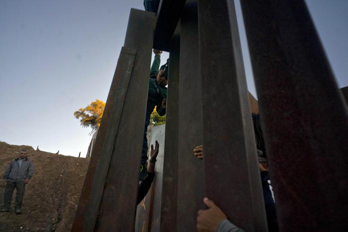 migrantes hondureños cruzan el muro desde tijuana hacia estados unidos.