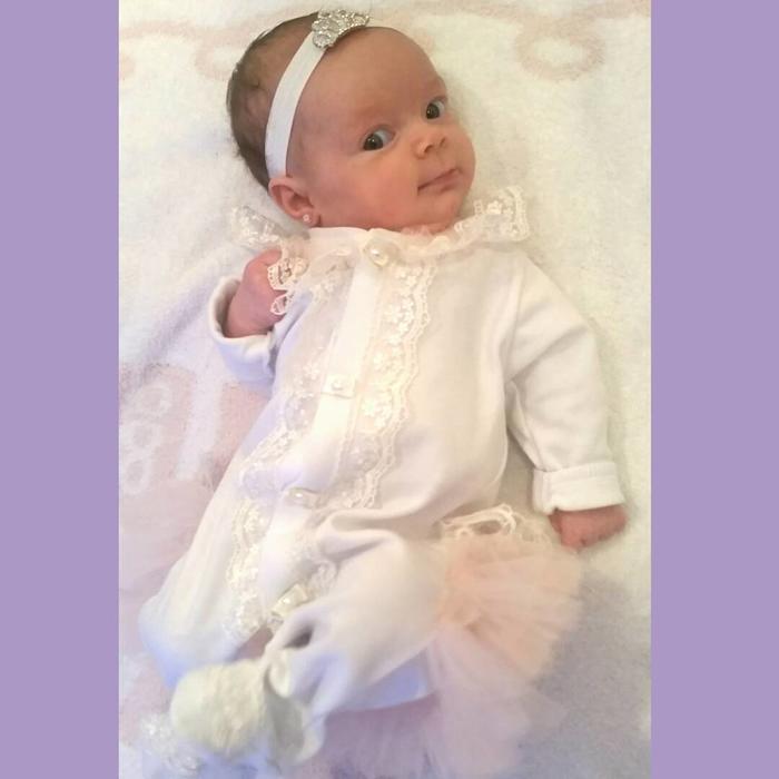 Chanel Nicole con ropa blanca acostada