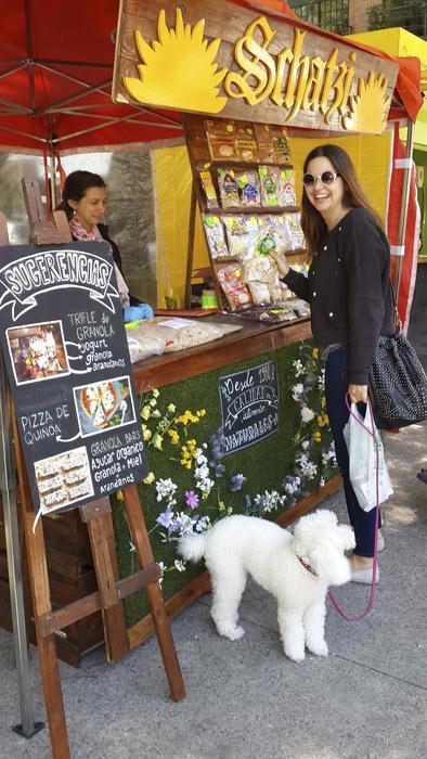 Mujer con perrito blanco comprando granola