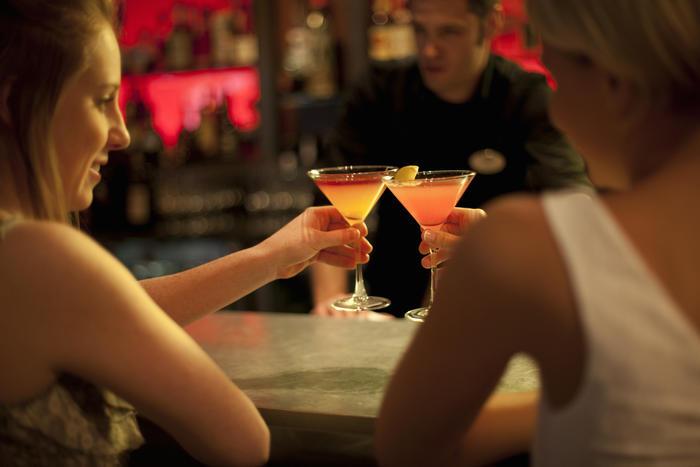 Mujeres jóvenes bebiendo en un bar.