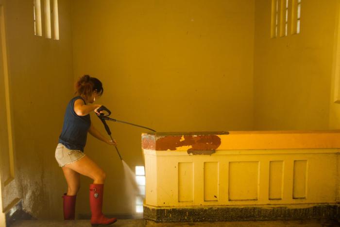 Una voluntaria usa una lavadora eléctrica para limpiar una de las escaleras en la escuela Pedro G. Goyco de San Juan.