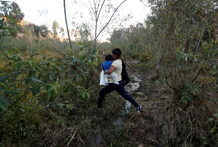 Yesenia Martínez, de 24 años, lleva a su hijo Daniel, de ocho meses de edad, mientras busca un lugar para cruzar el muro fronterizo de Estados Unidos para rendirse a la patrulla fronteriza y solicitar asilo.