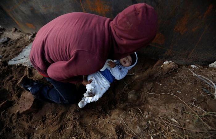 El migrante hondureño Joel Méndez, de 22 años, pasa a su hijo Daniel, de ocho meses de edad, a través de un agujero debajo del muro fronterizo de los Estados Unidos a su compañera, Yesenia Martínez, de 24 años, que ya había cruzado en Tijuana, México, el