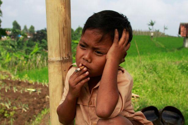 Dihan Awalidan fumando cigarrillo en un campo