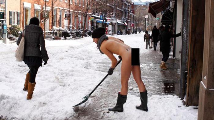 Foto de Erica Simone, fotógrafa desnuda paleando nieven en calle de Nueva York
