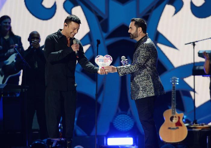 Enrique Santos entrega el Premio Corazón Latino iHeartRadio a Ricky Martin.