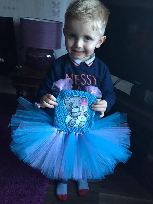 Hijo de Shona Campbell sosteniendo un vestido