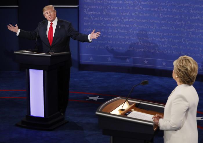 Trump speaks as Clinton listens during their third and final 2016 presidential campaign debate at UNLV in Las Vegas