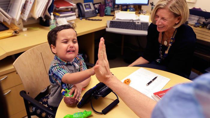 En una foto del jueves 22 de octubre de 2015, en Ann Arbor, Michigan, Grant Hasse llora mientras estrecha la mano del doctor Glenn Green, un cirujano pediátrico de vías respiratorias en el hospital infantil C.S. Mott de la Universidad de Michigan.