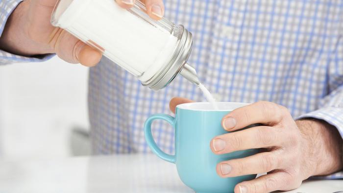 hombre sirve azúcar en taza