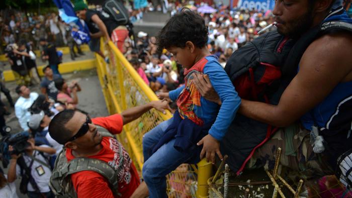 Un niño migrante es ayudado a cruzar la vaya de la frontera entre Guatemala y México