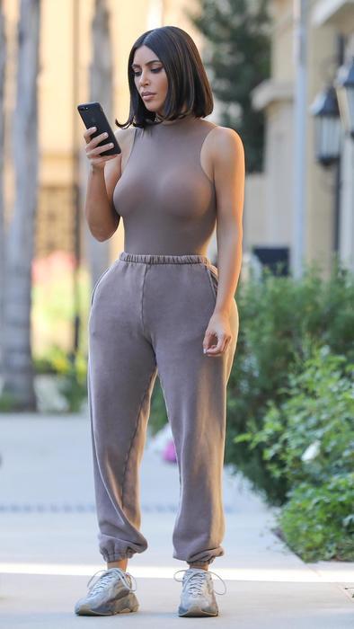 Kim Kardashina en ropa ajustada café mirando su teléfono